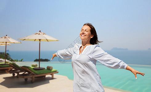 人与休闲的快乐的微笑的女人享受阳光无限的边缘游泳池的旅游度假背景快乐的女人无限的边缘游泳池上享受阳光图片