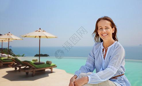 人与休闲的快乐的微笑女人无限的边缘游泳池的旅游度假背景快乐的女人无限的边缘池背景图片