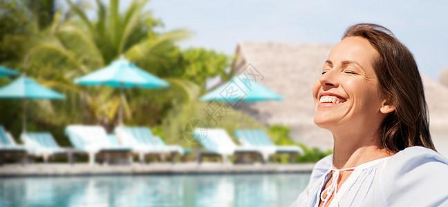 人与休闲的快乐的微笑女人享受阳光游泳池的旅游度假背景快乐的女人旅游胜地的游泳池上图片