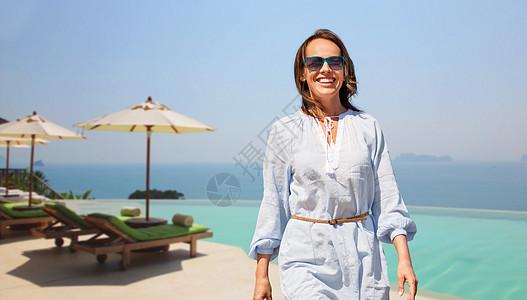 人与休闲的快乐的微笑女人走无限的边缘游泳池的旅游度假背景快乐的女人走过无限的边缘游泳池图片