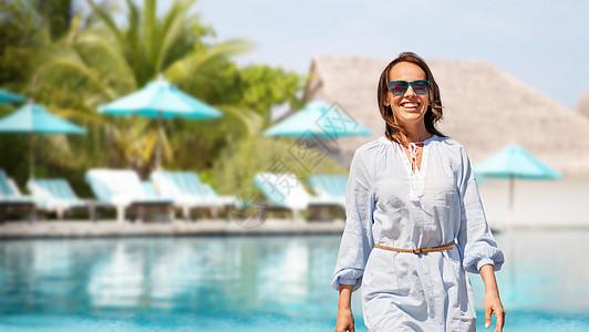 人与休闲的快乐的微笑女人走过游泳池的旅游度假背景快乐的女人旅游胜地的游泳池上图片