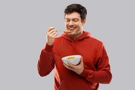 食物,早餐人们的微笑的轻人穿着红色帽衫,吃灰色背景的谷类食品微笑的轻人穿着红色帽衫吃谷物图片