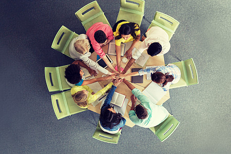 国际学生队围坐桌前看平板电脑图片