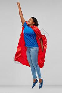 超级力量人的快乐的非裔美国轻女人超级英雄红色斗篷飞上灰色背景非裔美国女人超级英雄斗篷飞来图片