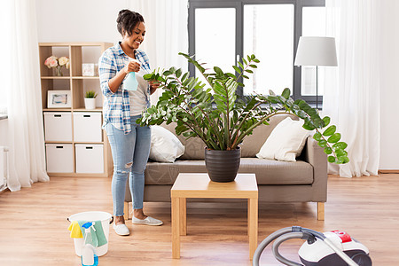 人,家务护理快乐的非裔美国妇女家庭主妇家里用喷水器喷洒室内植物快乐的非洲女人家里喷洒室内植物图片