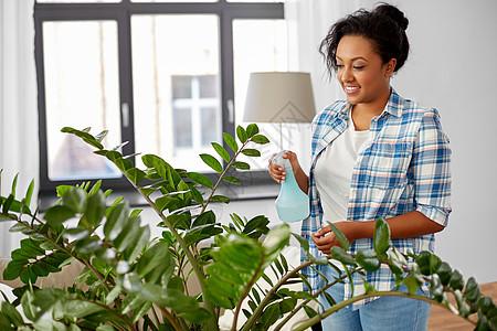 人,家务护理快乐的非裔美国妇女家庭主妇家里用喷水器喷洒家庭植物快乐的女人家里用水喷洒植物图片