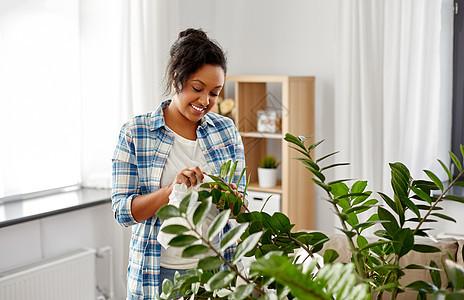 人,家务护理快乐的非裔美国妇女家庭主妇清洁家庭植物叶子的家里快乐的女人家打扫室内植物图片