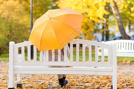 季节,雨天人们的女人带着雨伞坐秋天公园的长凳上带伞的女人坐秋天公园的长凳上图片