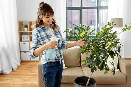 人,家务护理快乐的亚洲妇女家庭主妇家里用喷水器喷洒室内植物快乐的亚洲女人家里喷洒室内植物图片