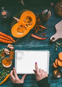 女手平板电脑上用手指指着,黑暗的厨房桌子上用橙色烹饪原料模拟屏幕南瓜红薯胡萝卜姜黄粉辣椒生姜,俯视图图片