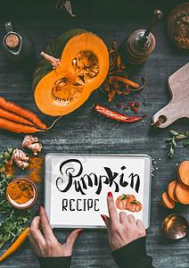 女手平板电脑上用手指指向文字刻字厨房桌子背景上的南瓜食谱,橙色烹饪原料红薯胡萝卜姜黄粉辣椒生姜图片