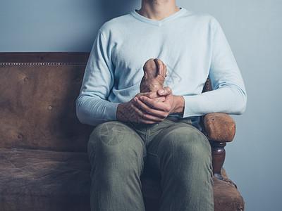 年轻人坐张旧沙发上,手里着个奇怪的红薯图片