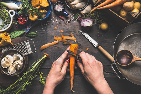 女女双手深色木制厨房桌子上剥胡萝卜,蔬菜烹饪原料勺子工具,俯视图图片