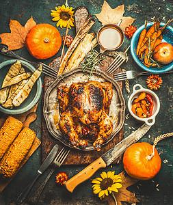 感恩节烤全塞鸡火鸡,配以酱汁南瓜玉米秋收蔬菜菜刀餐具,背景为黑暗的乡村背景,俯视图图片