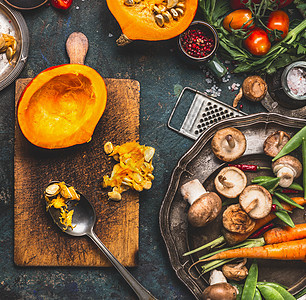 南瓜半砧板上,用勺子蘑菇蔬菜配料美味的素食烹饪,俯视图图片