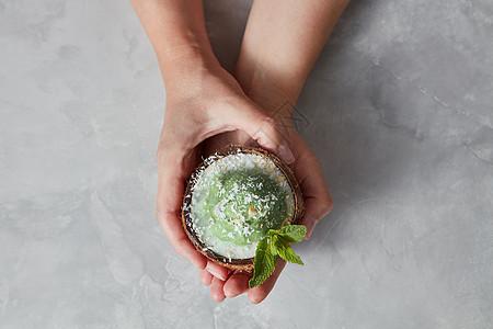 美味的绿色甜点,冰淇淋椰子壳里,女孩的手灰色的混凝土背景上,文字的地方俯视图妇女的手半椰子与美味的自制绿色冰淇淋与图片
