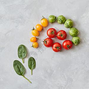红色黄色西红柿绿色菠菜叶片灰色背景上的成俯视图,平躺西红柿菠菜叶图片