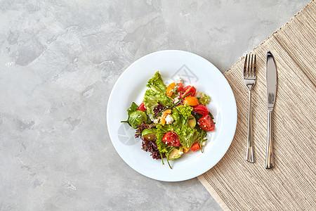 新鲜蔬菜奶酪的部分沙拉个盘子里,灰色的背景上叉子刀步步地端上菜,步的食谱中拍摄照片,俯视图,平躺新鲜蔬菜图片