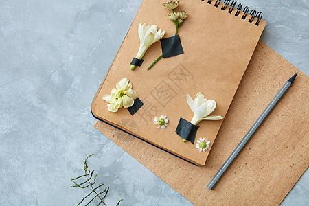 工艺笔记本的顶部视图与花装饰与铅笔混凝土背景,俯视图纸上的花卉装饰图片