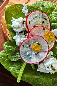 意大利传统自制的Bruschetta的特写片,菠菜奶酪与亚麻籽木制背景上的特写俯视图轻健康三明治与包烤包,软奶酪图片