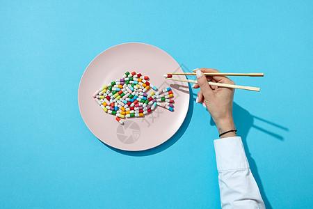 同的药丸补充剂鱼白色盘子筷子上的女人的手与阴影蓝色节食的抑制剂俯视图鱼彩色药丸药片个白色的盘子图片