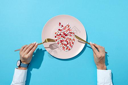 鱼五颜六色的药丸药片个白色的盘子,女孩的手与手表蓝色的背景与阴影,药丸心血管疾病的负影响俯视图维图片