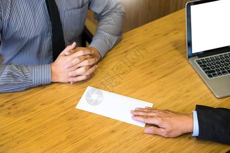 一名商人的手将辞职信最后报酬交给了执行老板在木制桌子上交给他的老板换工作失业概念图片