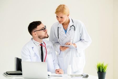 医院办公室的生负责桌上笔记本电脑工作另一名医生正在讨论病人的健康问题图片