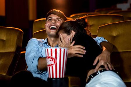 一对夫妇的causin在电影院看一部惊魂片女人的眼睛闭着把她的脸从屏幕上转开图片