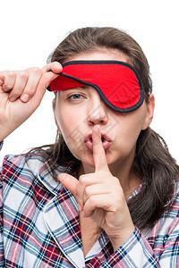 一个穿着睡衣的女人的肖像特写镜头手指放在嘴唇上一个穿着睡衣的女人的肖像特写镜头手指放在嘴唇上动作更安静图片