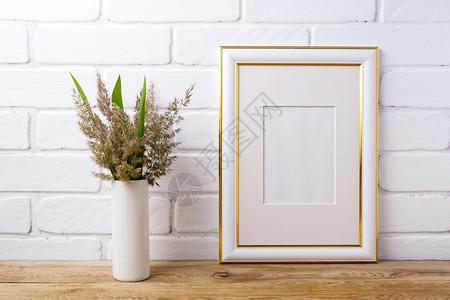 金色装饰框架在西里用草叶和绿制成的模型金色装饰框架在油漆砖墙附近用草和绿叶制成的圆柱形花瓶装成的模型空框架在展示艺术品时用空框架图片