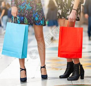 两只年轻成人的腿和购物袋紧贴在一起图片