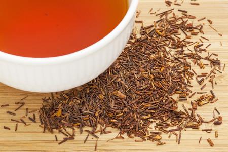 红茶罗奥伊波斯一杯白酒和竹木背景的松叶子来自南非红灌木的茶天然无咖啡因图片