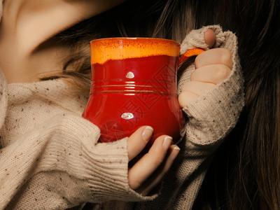 热饮喝杯红茶或咖啡的杯子由女亲手关闭穿着暖和毛衣的女人自己暖和图片