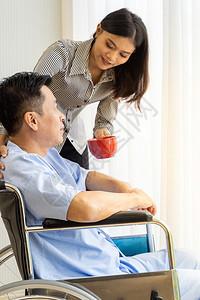 有红茶咖啡和坐轮椅亲属的老年人病正在透过窗户看图片