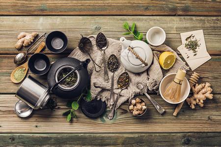 各种茶叶和壶成分干草药绿茶黑和木制叶平铺木制桌底各种茶壶和成分黑和木制桌底的红茶图片