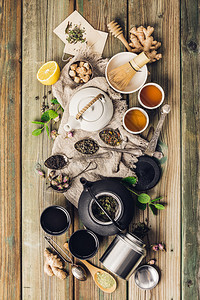 各种茶叶和壶成分干草药绿色黑茶和木制桌底的红茶平铺图片