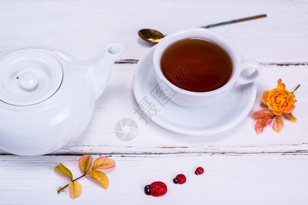 红茶装在一个白色的圆形杯子里茶托放在白色的木制背景上茶壶是白色的图片