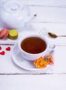 红茶放在一个白色的圆形杯子里茶碟放在白色的木制背景上在一个白色的茶壶后面图片