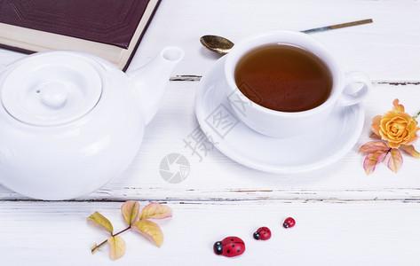 红茶放在一个带茶碟的圆形白色杯子里旁边是一个白色茶壶和一本合上的书图片