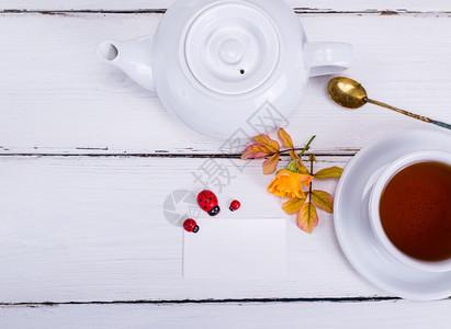 茶杯用红茶和白纸制成名片放在木制背景上顶视图图片