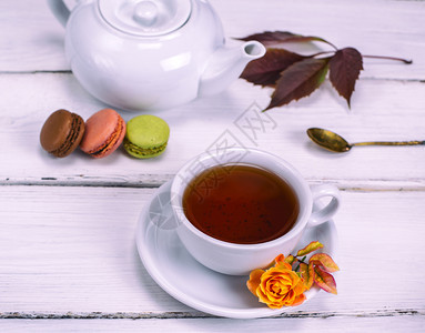 红茶在一个白色的圆形杯子里茶碟在白色的木制背景上蛋糕和麦卡龙图片