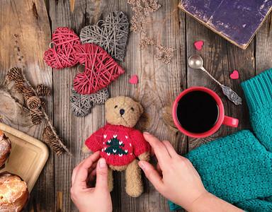 红茶杯黑咖啡和一只小泰迪熊红色毛衣灰木头背景图片