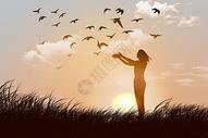 夕阳下草地上放飞鸽子的女人图片
