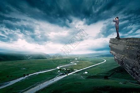 站在岩石上眺望未来的商务人士图片