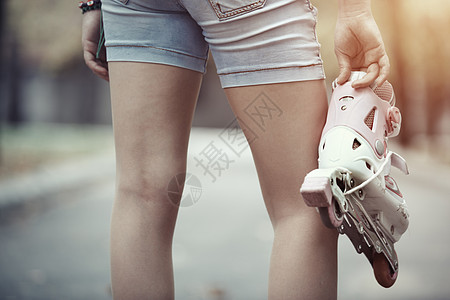 单手拎着轮滑鞋的人物图片