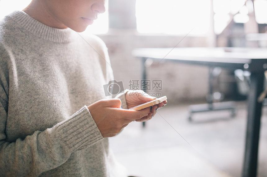教室里女子双手拿着手机图片