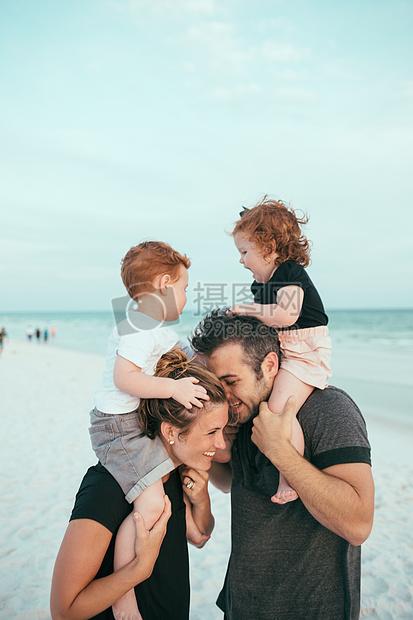 父母背着小孩海边游玩幸福家庭照图片