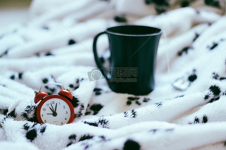 床上的杯子和闹钟图片