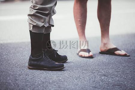 地面上穿皮靴和人字拖的人图片